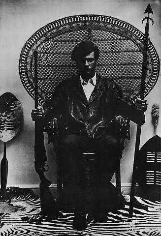 untitled (Huey P. Newton on a wicker peacock chair)